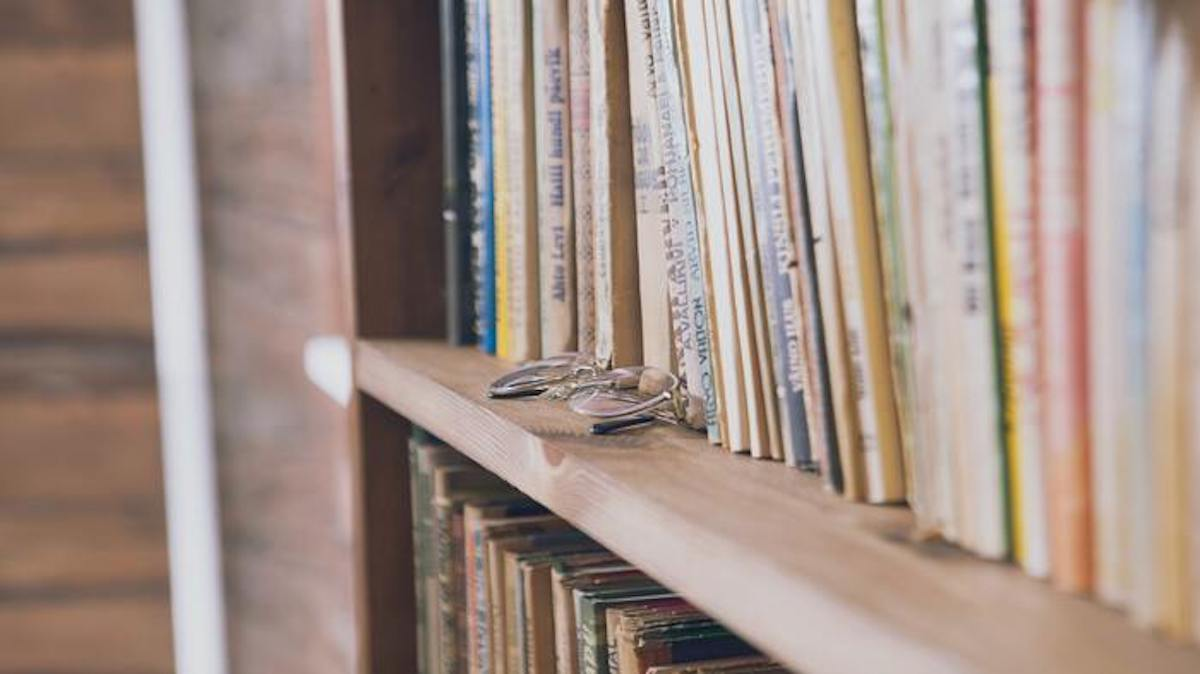 akiniai knygų lentynoje
