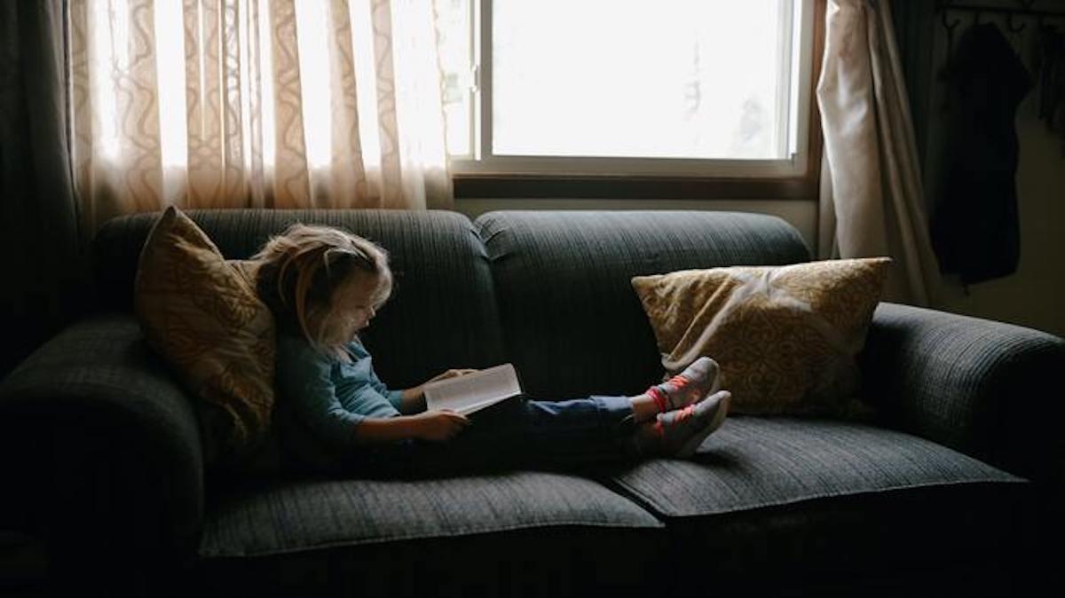 mergaitė skaito ant sofos